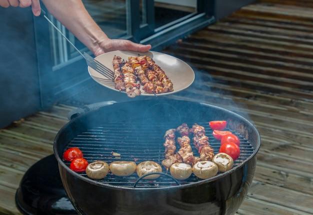 Assortimento di carne di pollo e verdure varie sulla griglia del barbecue cotte