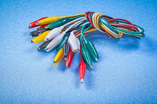 Assortimento di cavi a clip multicolore su superficie blu