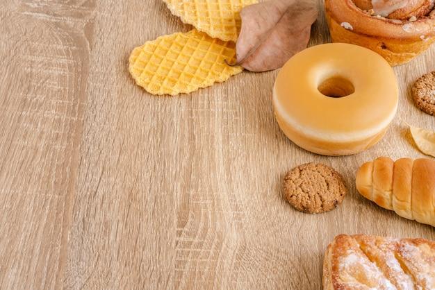 Assortimento di ciambella, cialde croccanti, pane cotto e dolci sulla superficie del tavolo in legno