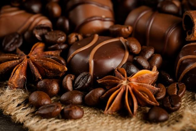 Assortimento di cioccolato bianco, fondente e al latte. cioccolato con panna, noci, mandorle, nocciole e cannella con chicchi di caffè. cibo dolce e nessun concetto di dieta.