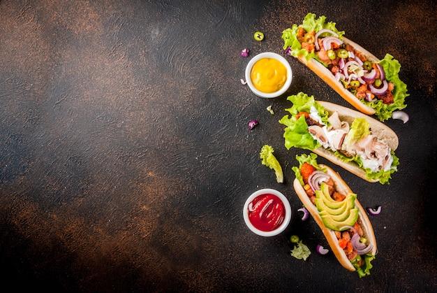 Assortimento di diversi hot dog vegani fatti in casa con carote, con cipolla fritta, avocado, peperoncino, funghi, pomodori e fagioli, vista dall'alto copyspace scuro arrugginito