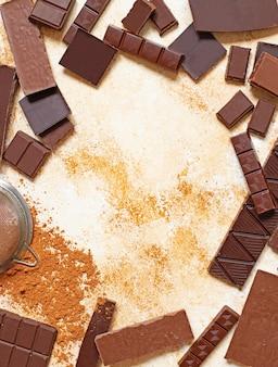 Assortimento di diversi tipi di cioccolato e cacao in polvere su uno sfondo di marmo chiaro. vista dall'alto, piatto. spazio per il testo
