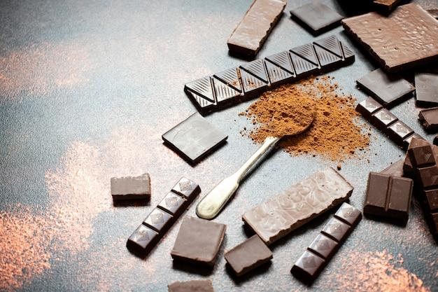 Assortimento di diversi tipi di cioccolato e cacao in polvere su uno sfondo scuro. avvicinamento. spazio per il testo