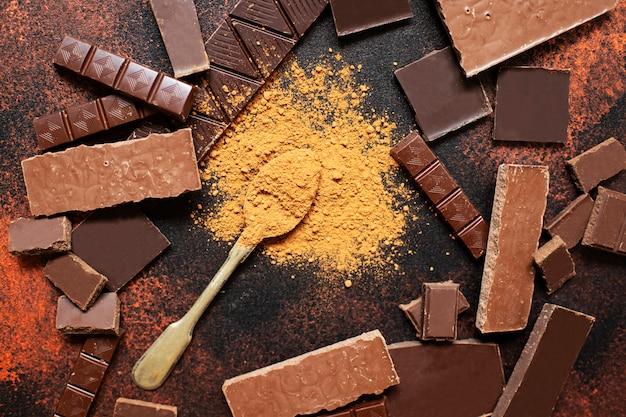 Assortimento di diversi tipi di cioccolato e cacao in polvere su uno sfondo scuro. vista dall'alto, piatto. spazio per il testo.