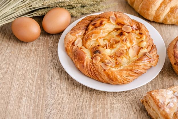 Assortimento di diversi tipi di pane, pasticceria, croissant, grano e uova freschi sulla superficie del tavolo in legno.