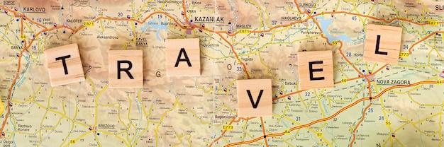 Assortimento di elementi da viaggio autunnali piatti con lettere in legno