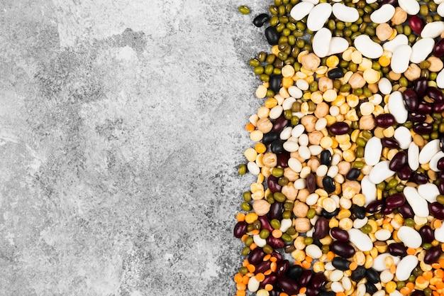 Assortimento di fagioli (lenticchie rosse, lenticchie verdi, ceci, piselli, fagioli rossi, fagioli bianchi, fagioli misti, fagioli verdi) su spazio grigio. vista dall'alto, copia spazio. spazio alimentare