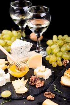 Assortimento di formaggio con noci, pane e miele su lastra di pietra ardesia,
