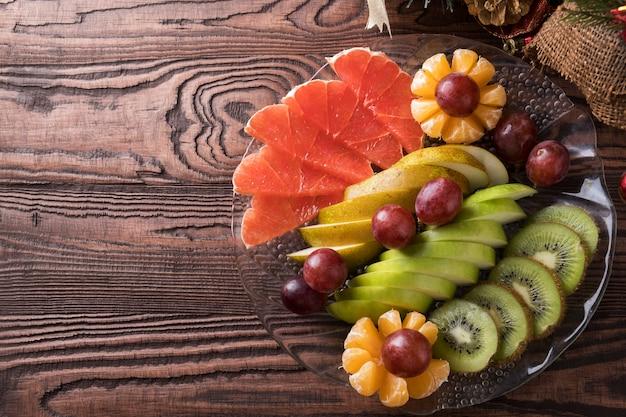 Assortimento di frutta a fette sul piatto. frutta fresca.