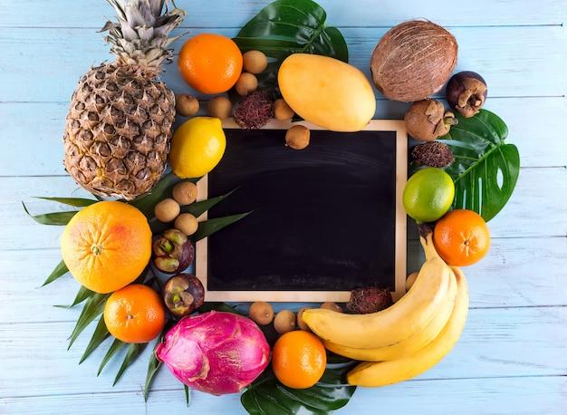 Assortimento di frutti tropicali con foglie di palme e lavagna