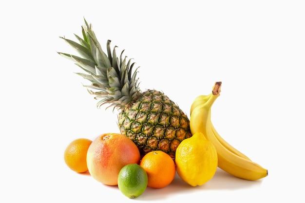Assortimento di frutti tropicali isolato su sfondo bianco. ananas, banane, arancia, lime, limone, pompelmo.