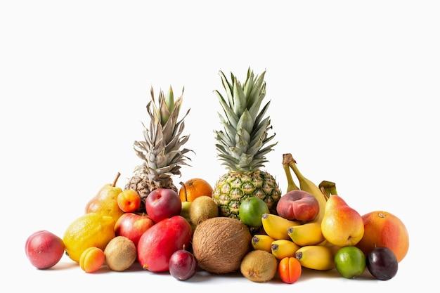 Assortimento di frutti tropicali isolato su sfondo bianco. ananas, cocco, banane, mango, mele, kiwi, lime, limone, pera, albicocche, pesche e prugne.