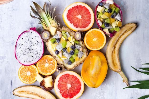Assortimento di frutti tropicali su un fondo leggero di pietra con foglia di palma. vista dall'alto. copia spazio