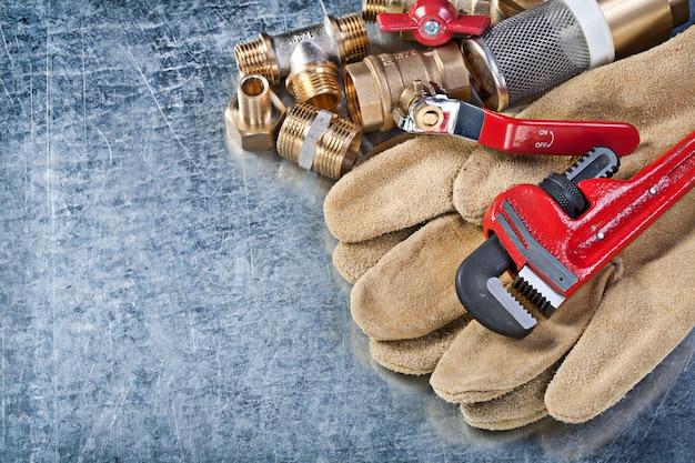 Assortimento di guanti di sicurezza per hardware in ottone per impianti idraulici su superficie metallica
