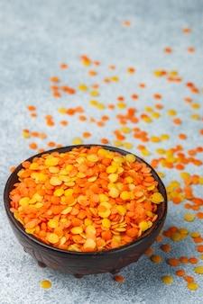 Assortimento di lenticchie multicolori asciutte in una ciotola di argilla
