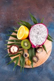 Assortimento di mezze frutti tropicali su un gioco rotondo in legno su un motivo di sfondo di pietra.