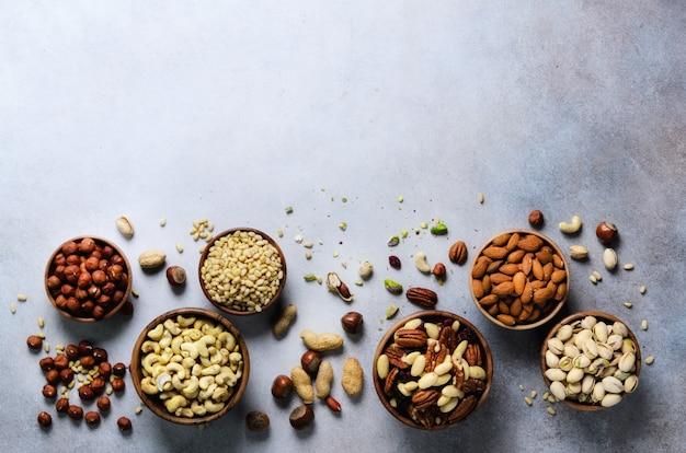 Assortimento di noci in ciotole di legno. anacardi, nocciole, noci, pistacchio, noci pecan, pinoli, arachidi, uvetta. miscela dell'alimento, vista superiore, spazio della copia ,.
