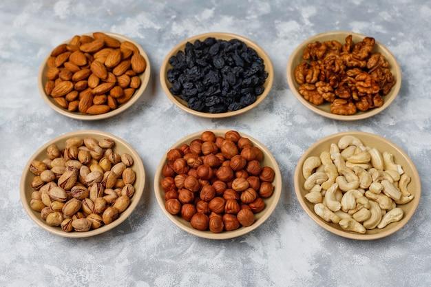 Assortimento di noci in piatti di ceramica. anacardi, nocciole, noci, pistacchi, noci pecan, pinoli, arachidi, uvetta.vista dall'alto
