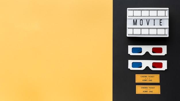Assortimento di oggetti cinematografici su sfondo bicolore con spazio di copia