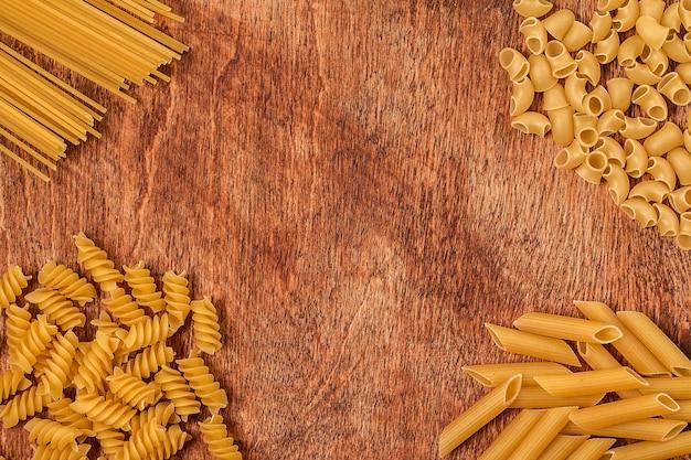 Assortimento di pasta di forma diversa sulla tavola di legno