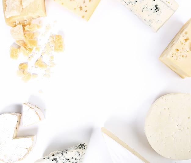 Assortimento di pezzi di formaggio, vista dall'alto, sfondo bianco copyspace