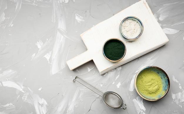 Assortimento di polvere organica in ciotole e tavola di legno
