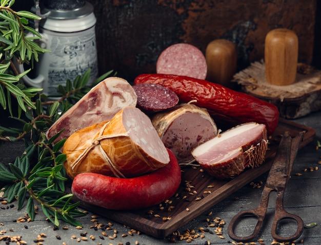 Assortimento di salumi salame, peperoni, prosciutto su tavola di legno