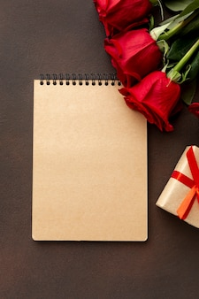 Assortimento di san valentino con le rose e il primo piano vuoto del blocco note