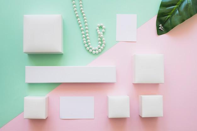 Assortimento di scatole bianche, collana e orecchini con nota adesiva su sfondo