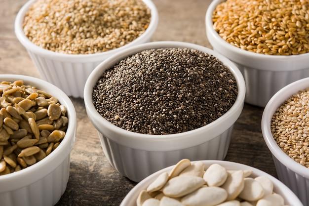Assortimento di semi diversi in ciotola sul tavolo di legno zucca, lino, chia, girasole e semi di sesamo