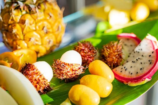 Assortimento di sfondo esotico tropicale cibo fresco. frutti esotici alimentari sani, vegani ed estivi. avvicinamento