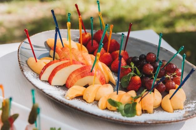 Assortimento di snack di frutta o finger food offerti agli ospiti a un ricevimento di matrimonio o una festa da parte della società di catering