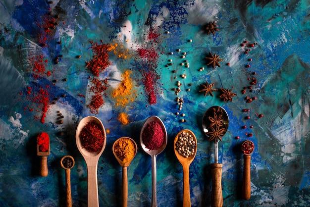 Assortimento di spezie naturali su un vintage cucchiai su cemento blu
