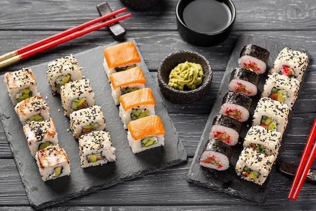 Assortimento di sushi maki ad alto angolo su ardesia con le bacchette