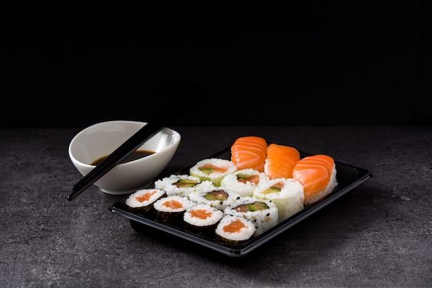 Assortimento di sushi sul vassoio nero e salsa di soia