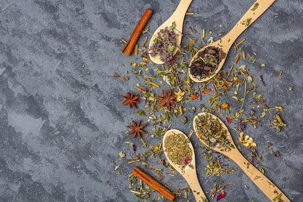 Assortimento di tè disseccato in cucchiai di legno con anice e cannella in stile rustico. tè biologico alle erbe, verde e nero con petali di fiori secchi per la cerimonia del tè. primo piano, copia spazio per il testo