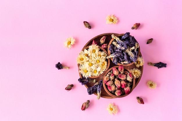 Assortimento di tè tropicale sano a base di erbe a secco in ciotole di legno su sfondo rosa.