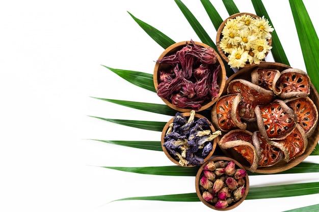 Assortimento di tè tropicale sano a base di erbe secco in ciotole di legno isolato su priorità bassa bianca.