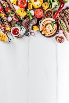 Assortimento di vari barbecue per grigliate di carne, barbecue party fest - shish kebab, salsicce, filetto di carne alla griglia, verdure fresche, salse, spezie, superficie di marmo bianco, sopra lo spazio della copia
