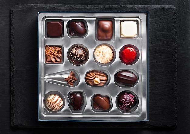 Assortimento di varietà di caramelle di cioccolato bianco e fondente di lusso in vassoio plastick d'argento su fondo di pietra nero