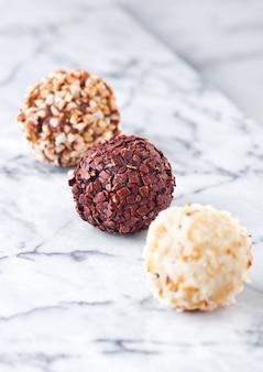 Assortimento di varietà di caramelle di cioccolato bianco e fondente di lusso su fondo di marmo bianco