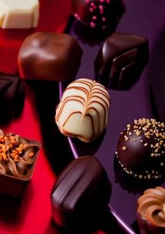 Assortimento di varietà di caramelle di lusso al cioccolato bianco e fondente sul piatto rosso e viola