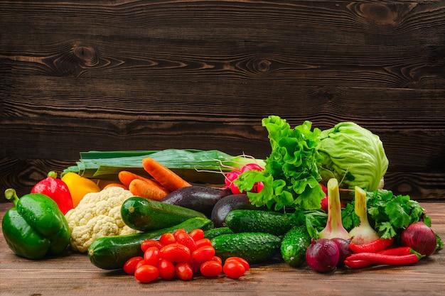 Assortimento di verdure fresche sulla parete di legno scuro