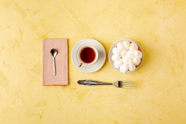 Assortimento piatto laico con tè e torta su sfondo giallo