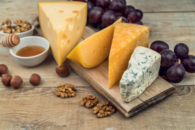 Assortimento saporito del primo piano di formaggio sulla tabella con le noci