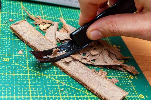 Assottigliamento della striscia di pelle marrone con lo strumento skiver. hobby artigianale in pelle