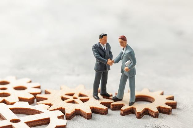 Assumere personale. selezione del leader del manager per l'azienda. gli uomini d'affari in giacca e cravatta si stringono la mano sugli ingranaggi come simbolo dei processi aziendali in azienda