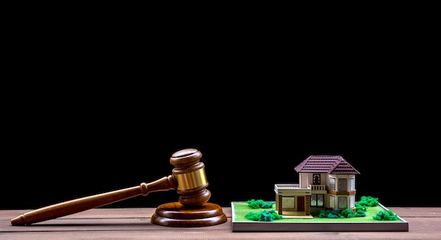 Asta di case, martello d'asta, simbolo di autorità e casa in miniatura