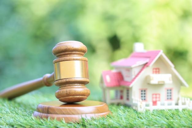 Asta di proprietà, martelletto in legno e casa modello su sfondo verde naturale, avvocato immobiliare di proprietà e concetto di proprietà