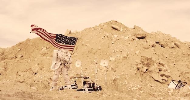 Astronauta con bandiera americana in piedi sulla montagna rocciosa del pianeta rosso alieno / marte. first manned mission on mars